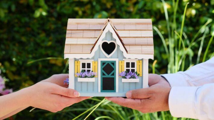 People holding a wooden miniature house